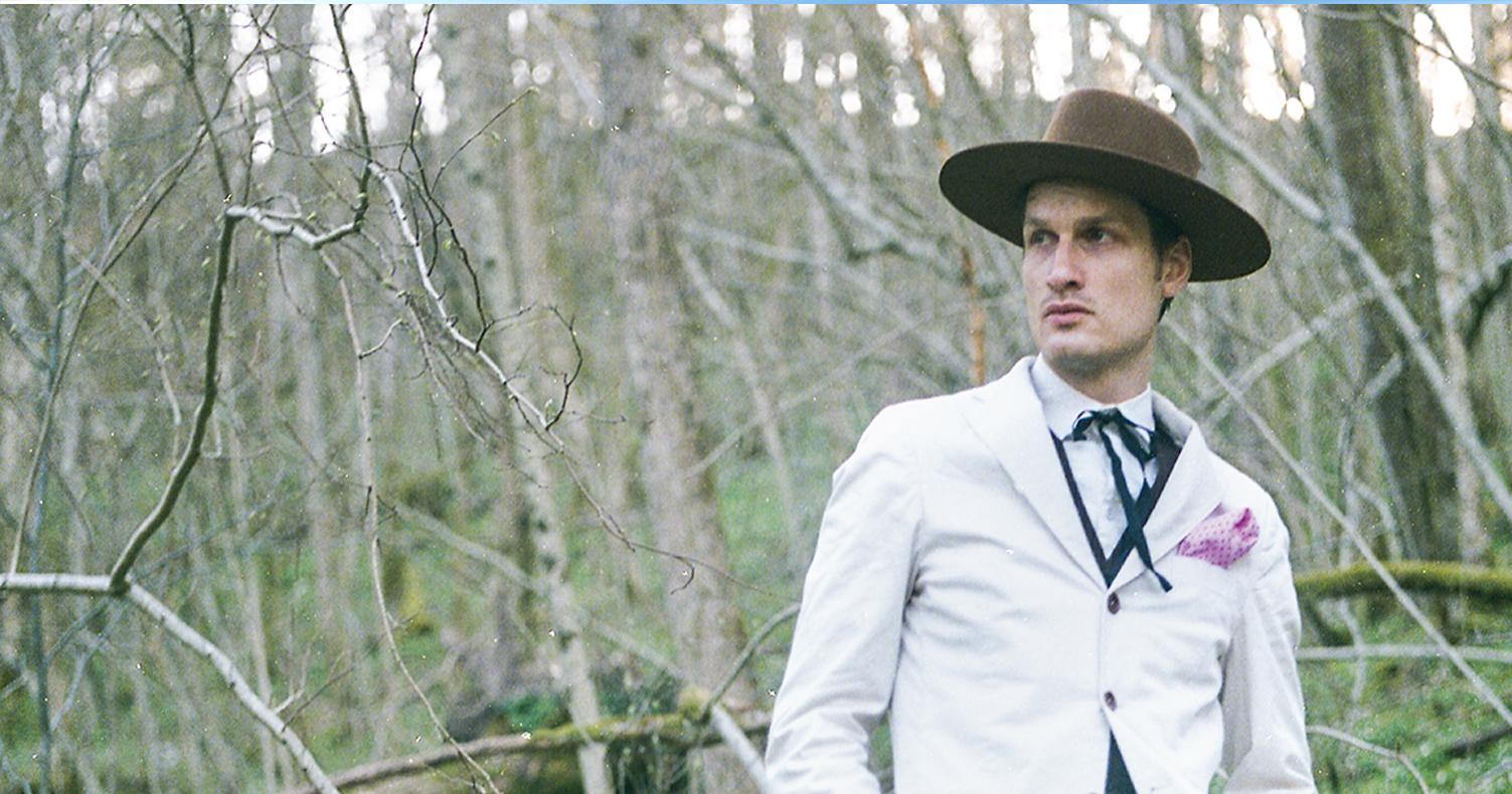 Bror Gunnar Jansson i vit kostym och brun hatt i skogen bland vitsippor.