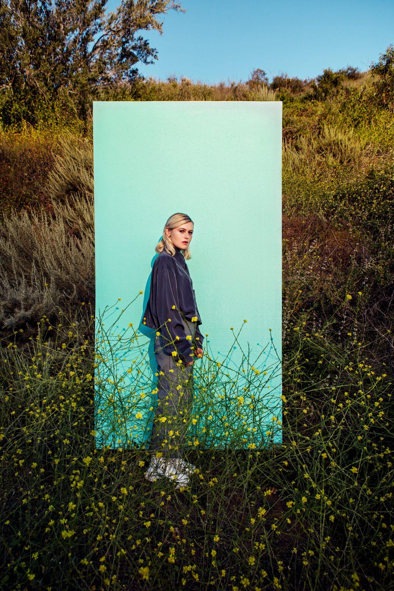 Ellen Krauss framför en mintgrön box ute i naturen.