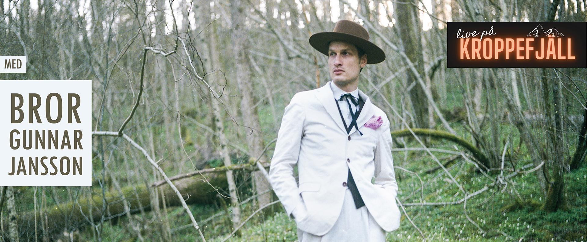 Bror Gunnar Jansson i vit kostym och hatt i skogen bland vitsippor