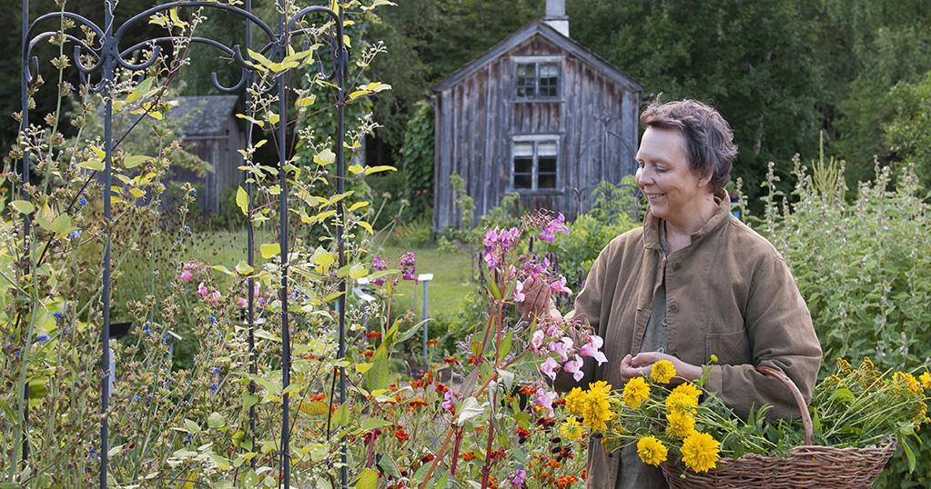 Kerstin Ljungqvist bland blommor i Örtagården i Dals Rostock.